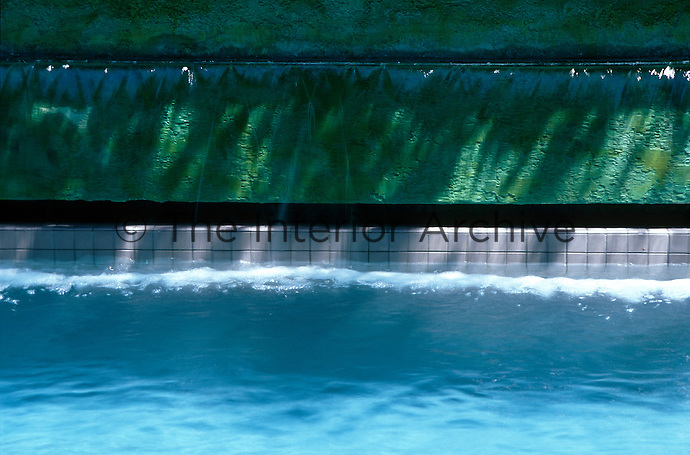 Close-up of a water curtain feature edging the swimming pool with copper patternated rendered wall and tiles