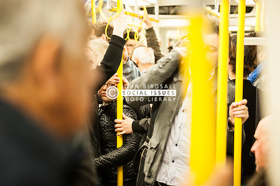 Commuters on a crowded London Underground tube train.