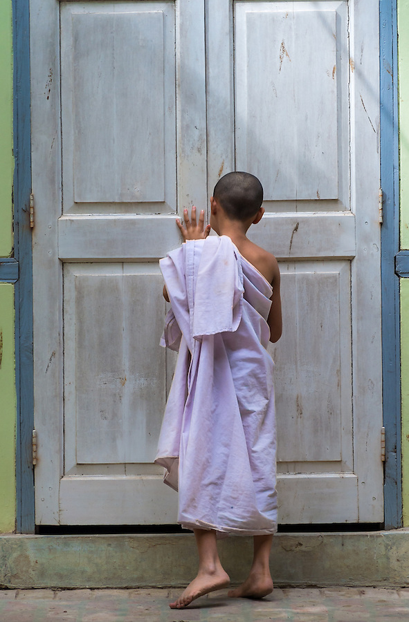 MANDALAY, MYANMAR - CIRCA DECEMBER 2013: Novice closing a door in a monastery  in Amarpura