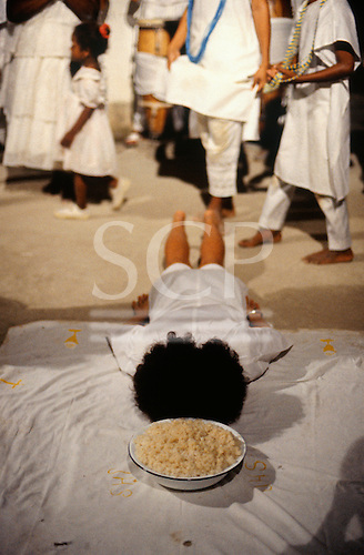 Recife, Pernambuco State, Brazil. Candomble religion: an initiate lies face down in front of food offering.