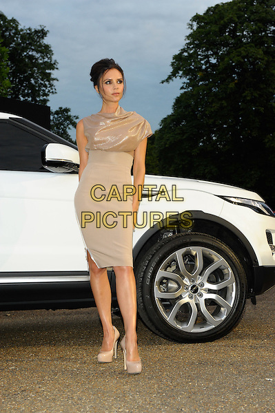 VICTORIA BECKHAM.Attends the Range Rover 40th Anniversary Party in association with Vogue at the Orangery, Kensington Palace, London, England, UK..July 1st 2010.full length beige gold shimmery shiny sparkly ruched top high waisted waist skirt nude shoes heels platform asymmetric new car model white vehicle posing .CAP/CJ.©Chris Joseph/Capital Pictures.