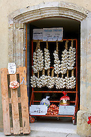 Plaits of garlic and bags of onions for sale, Bastide d'Armagnac, France