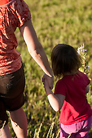 Young girl playing on grassy hill with Mother sister aunt, Steamboat Springs, Colorado