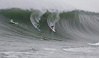 Evan Slater and Tyler Smith race down huge wave at Mavericks Surf Contest 2008.  Half Moon Bay, Ca.  January 12, 2008.