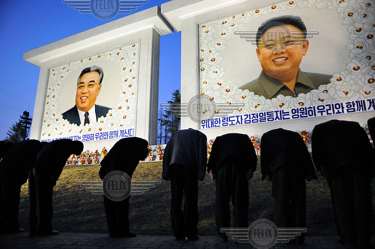People bow in homage to two new paintings of Eternal President Kim Il-sung and Supreme Leader Kim Jong-il (right), created for the birthday celebrations for Kim Il-sung...