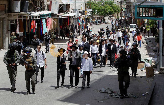 Israeli troops stand guard as Israeli settlers have a tour during the Jewish holiday of Passover in the West Bank city of Hebron, on April 26, 2016. Photo by Wisam Hashlamoun