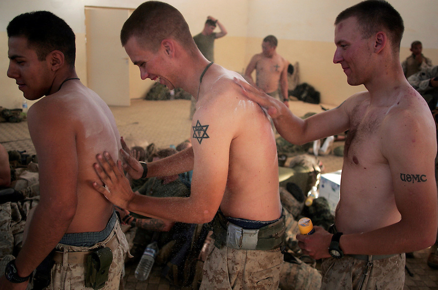The Marines of Kilo Co. 3rd Battalion 1st Marine Regiment (3/1) eat, relax, and treat themselves for heat rash and aching muscles after a long day of searching for insurgents and weapons in the Al-Anbar Province city of Haditha on Thursday, Oct. 6, 2005.