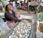 A woman sells eggs in a market in the Cambodian village of Maung Rossey.