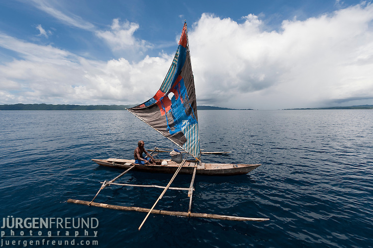 West Papuan fisherman in his outriggered dugout canoe with sails