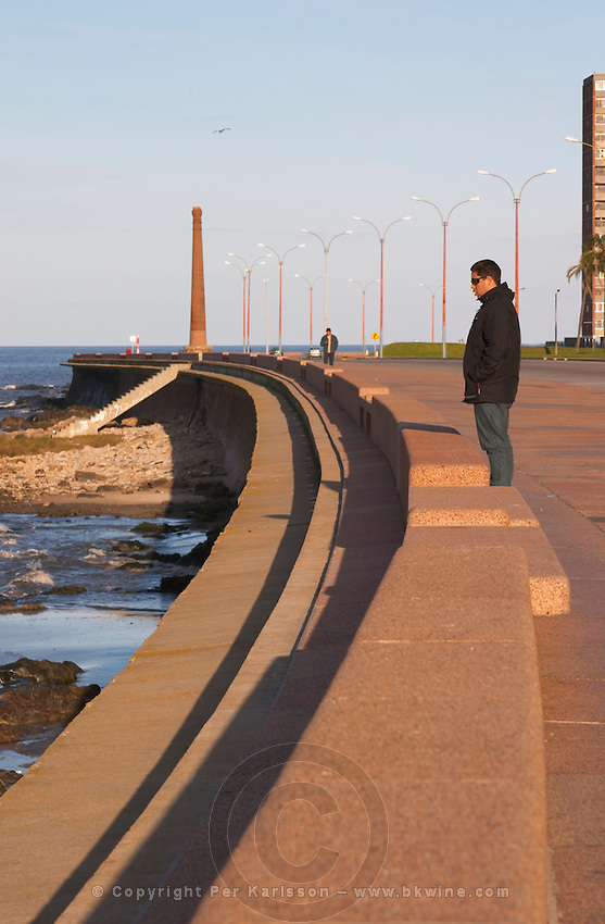 Coast line walk with a single lone man standing in the dawn sunshine in profile wearing sun glasses. Several lamp post forming a pattern and a chimney in the background. A man walking. Montevideo, Uruguay, South America