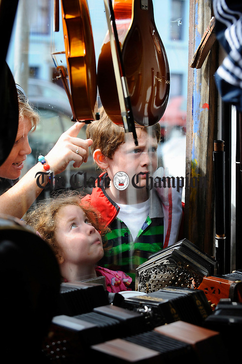 Niamh and Dermot O Brien of Lisnagry Limerick, with their mother Aisling, eyeing up some instruments on sale during the Willie Clancy Week at Miltown Malbay. Photograph by John Kelly.