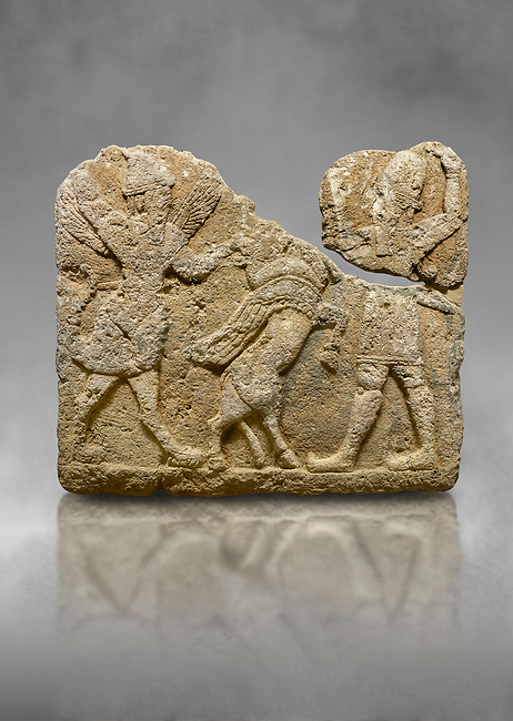 Hittite relief sculpted orthostat stone panel of Herald's Wall. Limestone, Karkamıs, (Kargamıs), Carchemish (Karkemish), 900-700 B.C. Anatolian Civilisations Museum, Ankara, Turkey.<br /> <br /> On the left is a winged mixed creature with a human head and body who has a scorpion tail and bird legs; on the right is a human-like god. The figures fight with a winged bull standing on its hind legs. The scorpion-man is known as Girtablull. <br /> <br /> Against a grey art background.