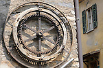 Detail of a giant old wheel that hangs on the side of a building in Moltrasio, a town on Lake Como, Italy.