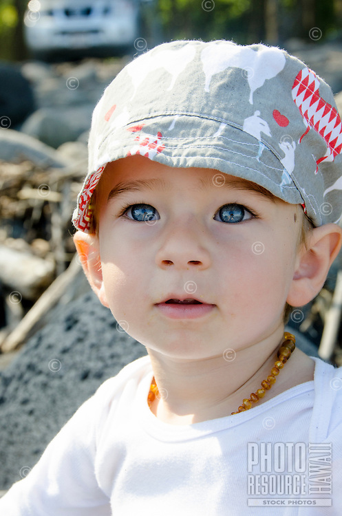 A young part-Asian local boy in a hat at the black sand beach of Waipi'o Valley, Big Island.