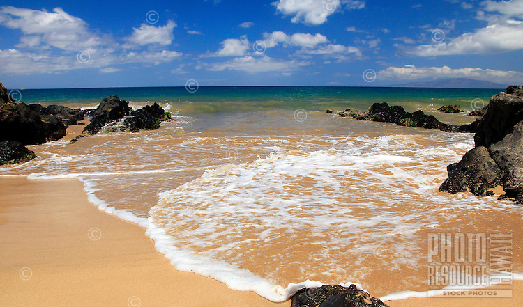 On a warm day, a foamy wave spreads out on Keawakapu Beach, Maui.