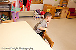 Education preschool 3-4 year olds boy sitting in time out for misbehavior horizontal