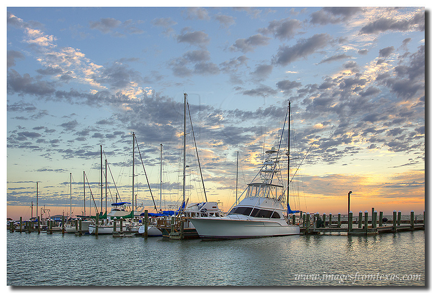 Morning comes to Rockport, Texas. The boats are quiet in the harbor on this fall morning. Out in the Texas Gulf waters, the sky begins to light up with oranges and blues. In the harbor, folks who are staying on houseboats begin to wake up. Not scene is this Rockport image shrimp boats returning from their search for food.