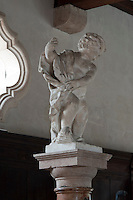 A detail of on of the individually hand-crafted cherubs which adorn the red marble columns the length of the stable