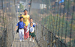 A mother walks her children to school across a suspension bridge over the Trishuli River near the village of Buttar in the Gorkha District of Nepal.