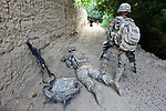 Spc. Bryce Esco, 25, of San Jose, Calif. probes a suspicious-looking area at the base of a mud wall, while Sgt. James Leatherwood, 25, of Dublin, Texas stands by with a mine detector in the village of Deh-e-Chowkay, in the Arghandab valley near Kandahar, Afghanistan. Seconds later, Esco discovered a length of detonation cord linking two jugs of homemade explosives together about 50 yards apart. The bomb-sniffing dog in the distance had passed the spot minutes earlier, but had not picked up scent.  May 26, 2010. DREW BROWN/STARS AND STRIPES