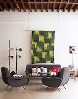 A colourful hand-printed textile creates a decorative focus in this warehouse living space
