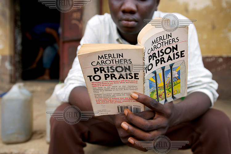 An inmate at Bo Prison reading the book 'PRISON TO PRAISE' by Merlin Carothers.
