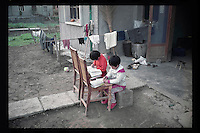 A pair of Chinese twin girls do their homework outside their house at a village in Jiangsu province, China, 1998.