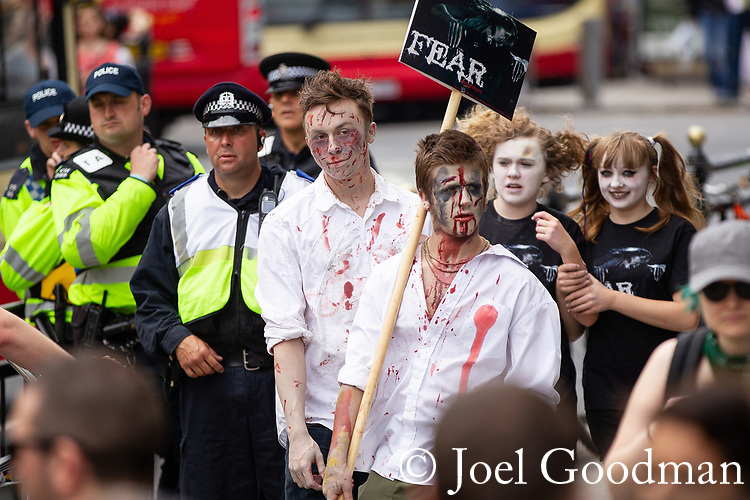 © Joel Goodman - 07973 332324 . 02/06/2012 . Brighton , UK . People dressed as zombies pass near demonstrators in Brighton . Groups of nationalists , including supporters of March for England and the EDL , congregate in Brighton as anti-fascist and left-wing campaigners supporting UK Uncut also congregate . An intensive policing operation is deployed to separate opposing left and right wing groups . Photo credit: Joel Goodman