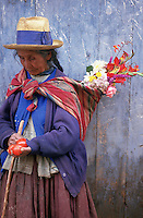 An old woman in Maras, near the Sacred Valley of the Incas, carrying flowers on her back.