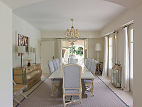 Three pairs of French windows opening on two sides allow free access from dining room to garden