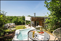 BNPS.co.uk (01202 558833)<br /> Pic: UniqueHomeStays/BNPS<br /> <br /> The Hide has great views from its hot tub.<br /> <br /> Bomb proof hideaway - the perfect place to cement a relationship...<br /> <br /> A concrete carport has been transformed into a ultra cool luxury staycation bolt hole - with even its fireplace, kitchen worktops and bath made from concrete. <br /> <br /> The Hide is perfect for romantic weekends away or creative solo escapes but it will set the minimalist traveller back up to &pound;2,350 a week in peak season.<br /> <br /> Despite its slightly industrial appearance, it is actually a cosy rural retreat, surrounded by nature at the end of a winding country lane three miles from Perranporth beach in north Cornwall.<br /> <br /> Unique Home Stays used a bird hide as the inspiration with quirky stick-out windows that allow guests to stargaze from the bed and lighting designed to replicate the effect of sunlight through trees.