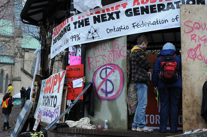 November 23, 2011, Toronto Police deployed in significant numbers this morning, beginning the process of evicting the Occupy Toronto tent camp from St. James Park.  Here, two unidentified protest supporters look in on those holding out in the band shell.