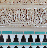 Detail of ceramic tiles in geometric designs and koranic inscriptions in carved stucco on the walls of the Patio of the Gilded Room, between the Mexuar and the Gilded Room or Cuarto Dorado, built under Mohammed V in the 14th century, in the Comares Palace, Alhambra Palace, Granada, Andalusia, Southern Spain. The Alhambra was begun in the 11th century as a castle, and in the 13th and 14th centuries served as the royal palace of the Nasrid sultans. The huge complex contains the Alcazaba, Nasrid palaces, gardens and Generalife. Picture by Manuel Cohen