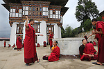 Buddhist monks practising their debating skills at Nalanda Buddhist Monastery, Punakha, Bhutan..Bhutan the country that prides itself on the development of 'Gross National Happiness' rather than GNP. This attitude pervades education, government, proclamations by royalty and politicians alike, and in the daily life of Bhutanese people. Strong adherence and respect for a royal family and Buddhism, mean the people generally follow what they are told and taught. There are of course contradictions between the modern and tradional world more often seen in urban rather than rural contexts. Phallic images of huge penises adorn the traditional homes, surrounded by animal spirits; Gross National Penis. Slow development, and fending off the modern world, television only introduced ten years ago, the lack of intrusive tourism, as tourists need to pay a daily minimum entry of $250, ecotourism for the rich, leaves a relatively unworldly populace, but with very high literacy, good health service and payments to peasants to not kill wild animals, or misuse forest, enables sustainable development and protects the country's natural heritage. Whilst various hydro-electric schemes, cash crops including apples, pull in import revenue, and Bhutan is helped with aid from the international community. Its population is only a meagre 700,000. Indian and Nepalese workers carry out the menial road and construction work.