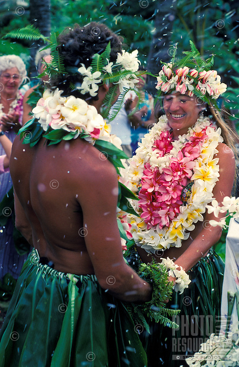 A wedding couple adorned only in ti leaves and flowers clasp hands and smile as flower petals are scattered over them