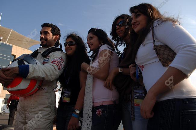 Bahraini girls posed with Bahraini driver Salman Al Khalifa just before the start of the  Formula BMW World Final at the Bahrain International Circuit, Bahrain, December 16, 2005.
