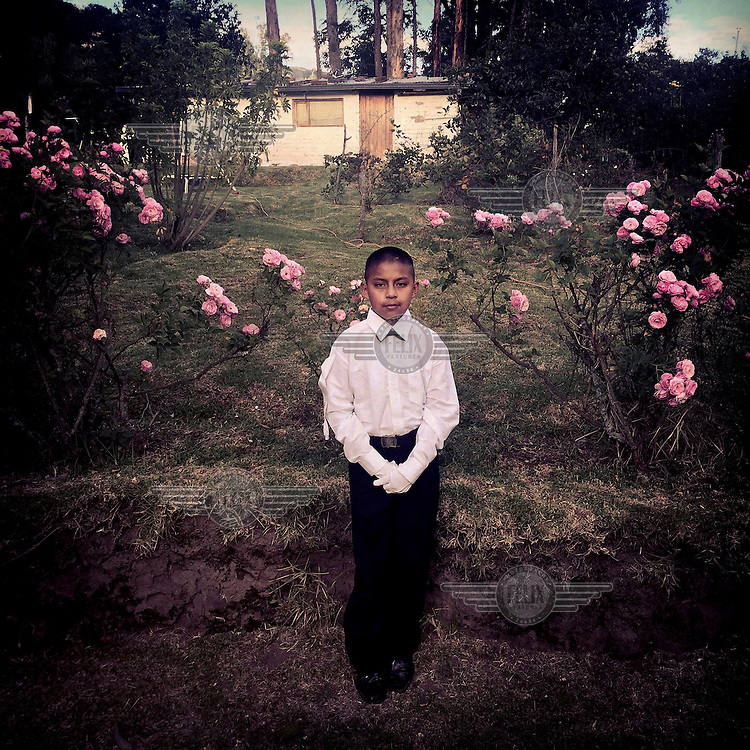 Andres Achance, 11, stands in front of his house before walking to the local church for his first communion ceremony.
