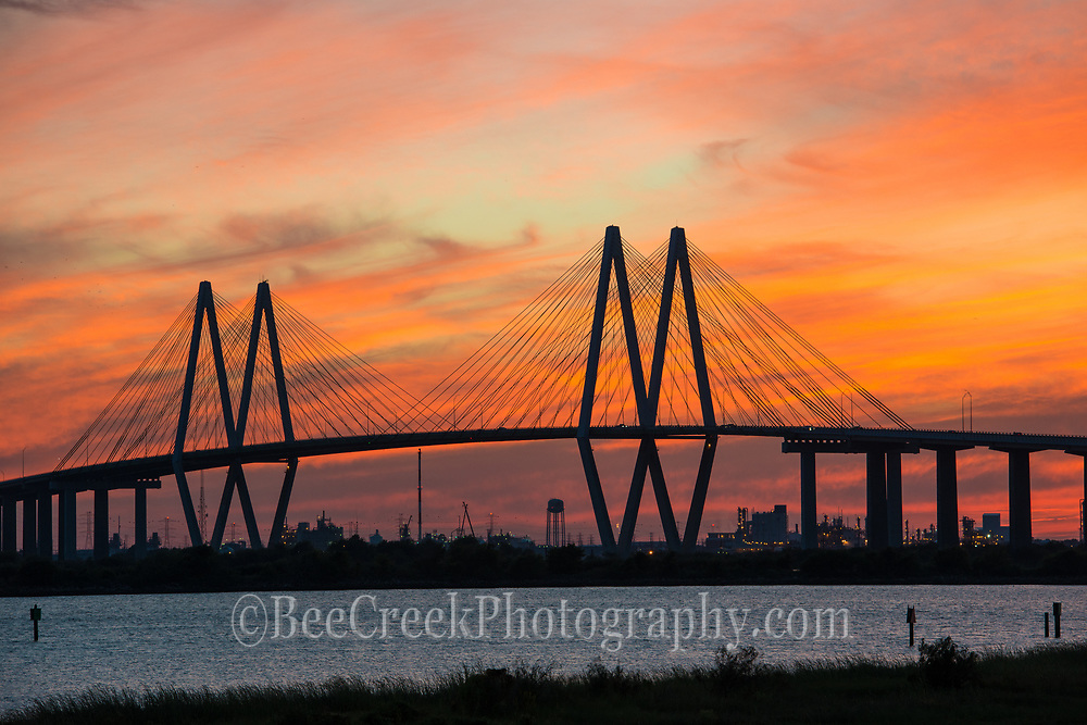 Fred Hartman bridge over the ship channel with this fiery orange glow sky after the sun goes down and the sky back lights this wonderful glow.The bridge was named after the Fred Hartman the  editor and publisher of the Baytown Sun from 1950-1974. This bridge is 2.6 miles long and spans across the ship channel from Baytown to La Porte Texas. The ship channel is a cable stay bridge and is the longest bridge of it type in Texas.  This bridge is the 77 largest in the world and one of four in Texas. The sky was incredible in this area on this day.