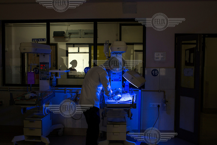 A nurse checks a premature baby sleeping beneath a phototherapy light in the postnatal intensive care unit at Duncan Hospital.