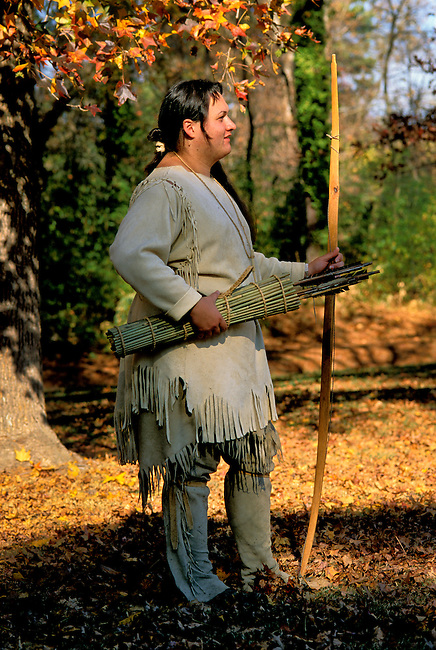 Historical interpreter demonstrates the bows; quivers and arrows that the Powhatan Indians used to hunt game such as deer at the Powhatan Indian Village on the Jamestown Settlement near Williamsburg; Virginia