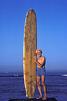 Old time surfer Arthur Reese with his longboard