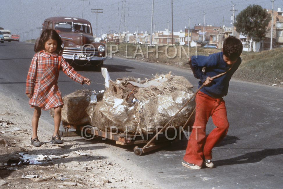 Young children haul garbage down a highway in Bogota, Colombia - Child labor as seen around the world between 1979 and 1980 - Photographer Jean Pierre Laffont, touched by the suffering of child workers, chronicled their plight in 12 countries over the course of one year.  Laffont was awarded The World Press Award and Madeline Ross Award among many others for his work.