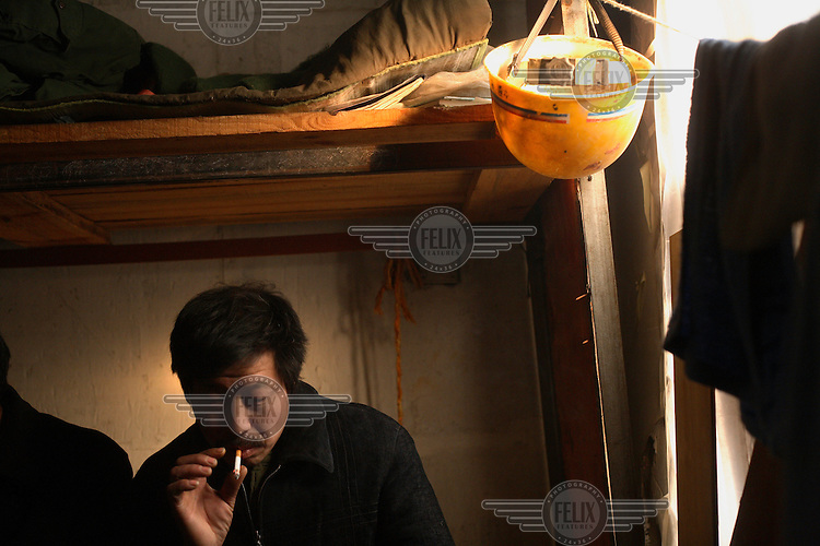 A migrant worker who came to work on the Olympic Games venues smokes a cigarette on his bed in the worker's living compound. ...