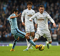 Picture by Howard Roe/AHPIX.com. Football, Barclays Premier League; <br /> Manchester City v Swansea City ;22/11/2014 KO 3.00 pm <br /> Etihad Stadium;<br /> copyright picture;Howard Roe;07973 739229<br /> Swansea's       Gylfi Sigurdsson tussles with    Manchester's Fernandindo
