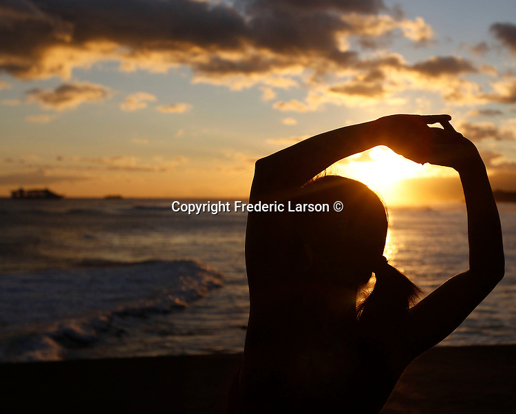 A woman does her stretching exercises at sundown on rodeo Beach, Marin County, California.