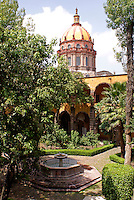 Dome of Templo de la Concepcion church and interior of the courtyard of  the Escuela de Bellas Artes or El Nigromante in San Miguel de Allende, Mexico. San Miguel de Allende is a UNESCO World Heritage Site.