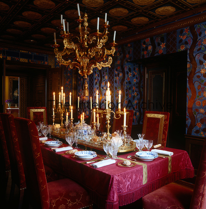 The dining room has a trompe l'oeil coffered ceiling and walls covered in stamped leather decorated with trees