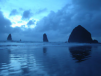 Silhouettes of Haystack Rock and the nearby Needles reflect in the high tide during sunset at Cannon Beach, Oregon, USA.  Haystack Rock, a protected wildlife refuge, is a Pacific coast landmark towering 235 ft. above the beach.