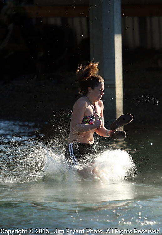 A Polar participant jumps off the bridge into the Burley Lagoon during the 31st annual Polar Bear on January 1, 2015 in Olalla, Washington. Over 500 hardy participants joined in on the annual New Year's Day Tradition by jumping into the chilly lagoon waters during the annual Polar Bear Plunge.  ©2015.  Jim Bryant Photo. All Rights Reserved.