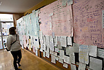 A woman looks at at messages written by tsunami survivors searching for friends and loved ones at an evacuation shelter in Rikuzentakata, Iwate Prefecture, Japan on  5 April 20011.  With phone lines down and postal services interrupted, survivors used such message boards to communicate with displaced friends and relatives. .Photographer: Robert Gilhooly
